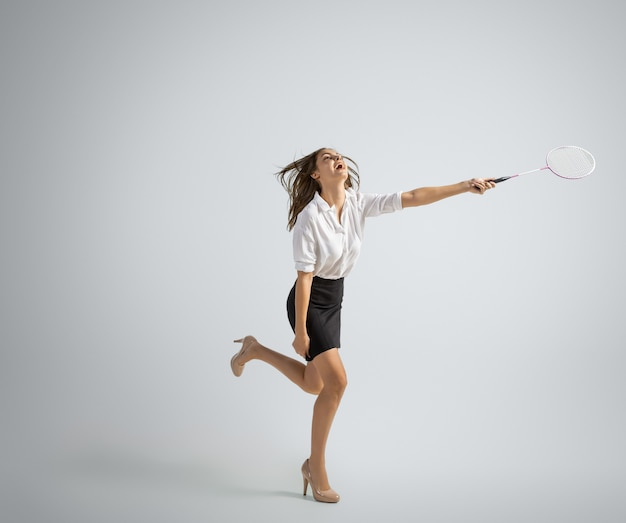 Caucasian woman in office clothes plays badminton on grey
