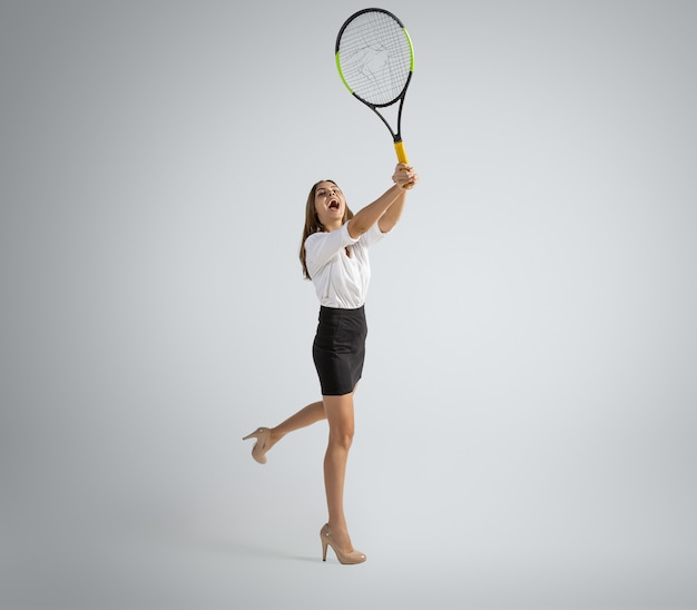 Caucasian woman in office clothes plays tennis on grey