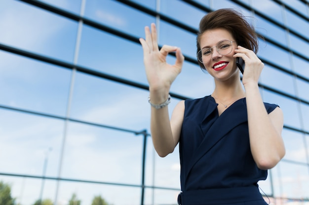 Caucasian woman in office clothes talking by telephone near the office building