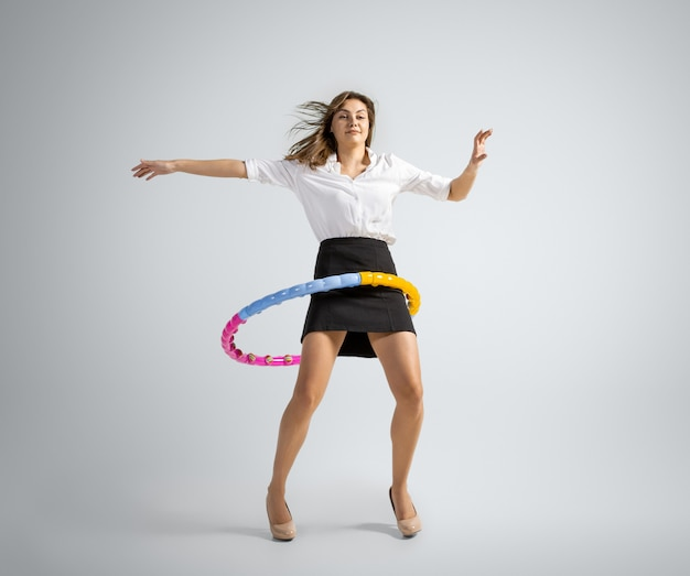 La donna caucasica in vestiti dell'ufficio che si allena con il cerchio isolato sul muro grigio