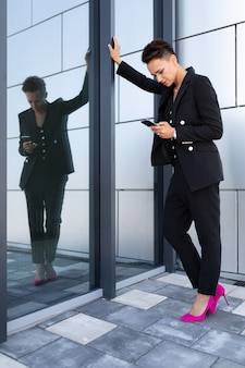 Caucasian woman in office clothes waits colleague near office building