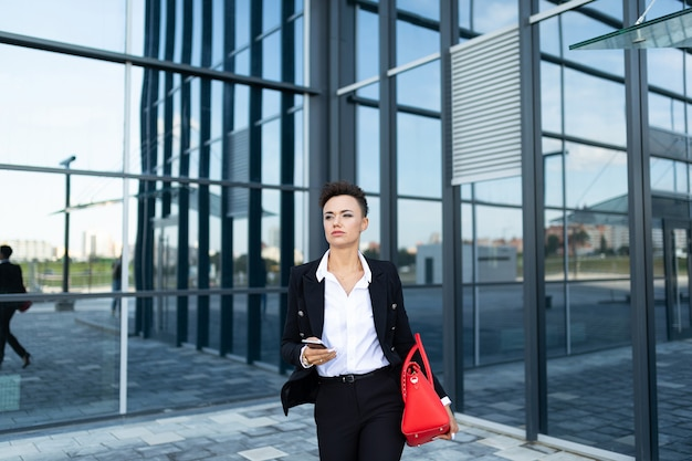 Caucasian woman in office clothes and with red bag waits colleague near office building