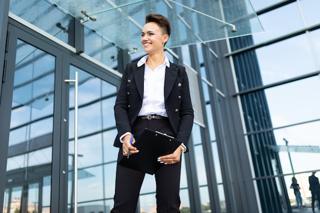 Caucasian woman in office clothes with tablet waits colleague near the office building