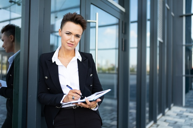 Caucasian woman in office clothes writes to notebook and waits colleague near the office building