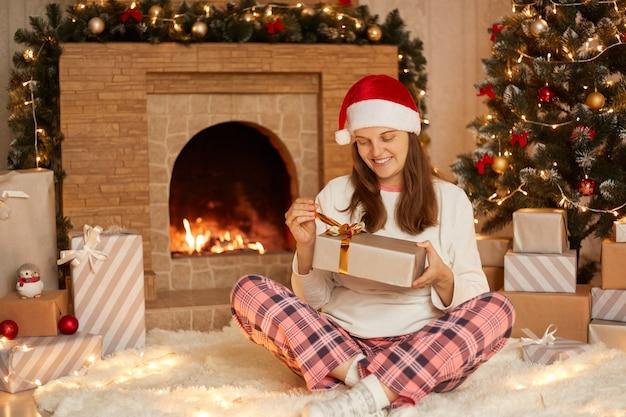 축제 거실, 체크 무늬 바지, 흰색 셔츠와 산타 클로스 모자를 쓰고 집에서 크리스마스를 축하하는 아가씨에 앉아있는 동안 선물 상자를 여는 백인 여자.