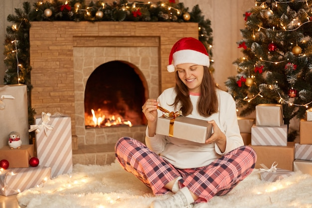 Caucasian woman opening present box while sitting on soft carpet in festive living room, lady wearing checkered pants, white shirt and santa claus hat, celebrating christmas at home.