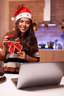 Donna caucasica che apre il regalo in videochiamata