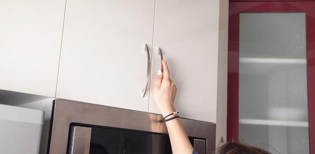 白人女性がキッチンのドアの家具を開きます。