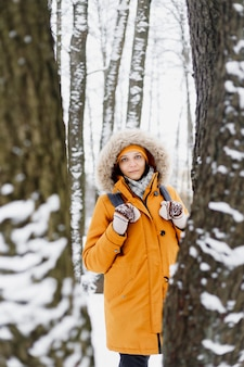 Caucasian woman in orange jacket walking in a winter park in the middle of the trees, portrait of a woman in nature, who enjoys a walk and the winter landscape