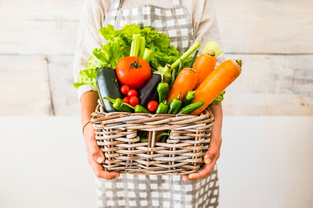 Caucasian woman people with bucket full of coloured and mixed fresh healthy food like fruit and vegetables