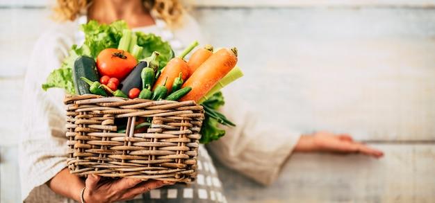 果物や野菜のような色と混合の新鮮な健康食品でいっぱいのバケツを持つ白人女性の人々