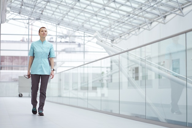 Caucasian woman physician cheerfully walking in white corridors of clinic
