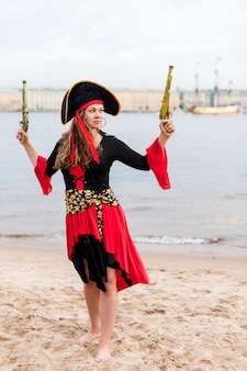 Caucasian woman in pirate costume raised to the top two toy guns.