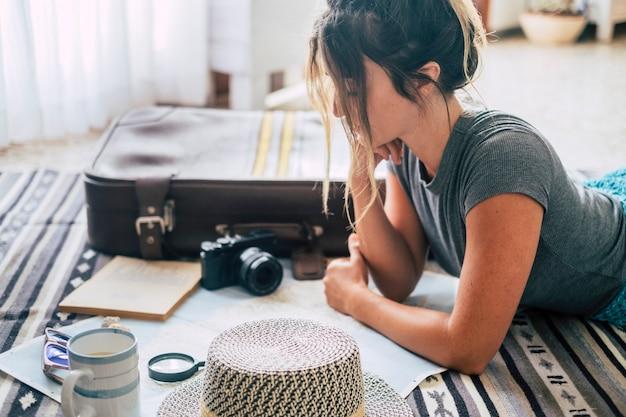 自宅で地図とガイド付きの休暇旅行を計画している白人女性、女性は床でリラックスしながら次の休暇休暇を計画します