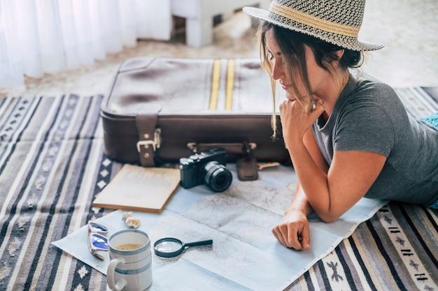 Кавказская женщина планирует путешествие в отпуск с картой и гидом дома, женщины планируют следующий отпуск, отдыхая на полу