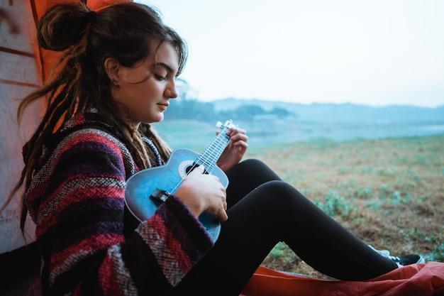 Кавказская женщина играет на гитаре после пробуждения