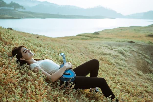 Кавказская женщина играет на гитаре у озера с одеялом