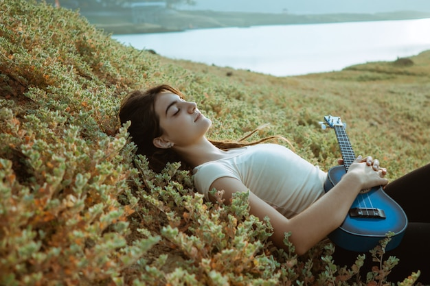 Caucasian woman playing guitar by a lake with blanket