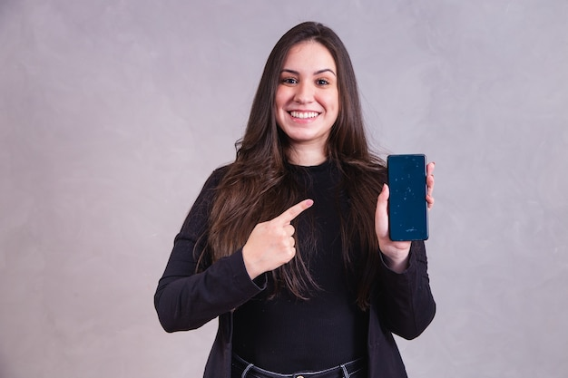 Caucasian woman pointing at cellphone with space for text on gray background.