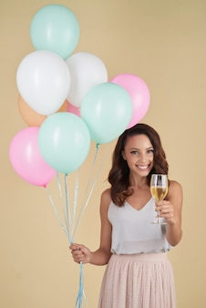 Caucasian woman posing in studio with bunch of helium balloons and champagne
