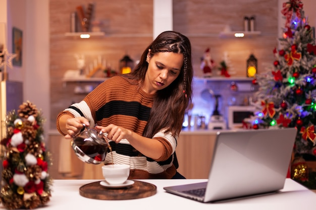 Caucasian woman pouring cup of tea from kettle