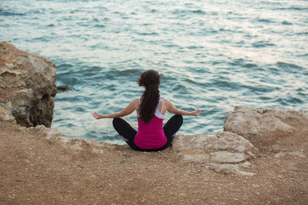 Кавказская женщина упражнениями йоги на берегу океана