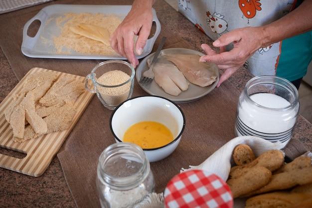 白人女性は昼食、魚の切り身の食べ物を準備します。家庭用厨房の高齢者。食材の背景