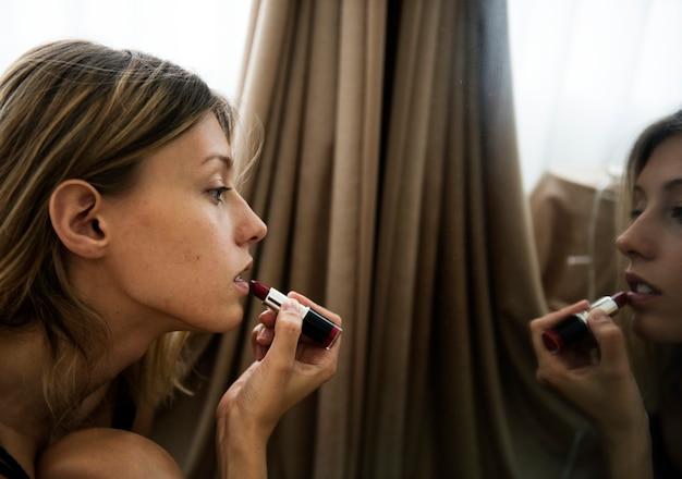 A caucasian woman putting on a lipstick