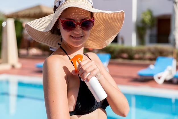 여름 날에 햇빛 아래 수영장에서 그녀의 어깨에 태양 크림을 넣어 백인 여자. 휴가, 태양 보호 요소 개념.