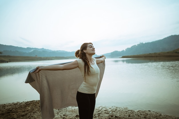 Caucasian woman raising arms with blanket