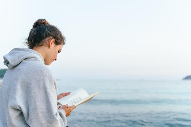 Caucasian woman reading a book on a bridge over the sea at magaluf beach. palma de mallorca, spain.