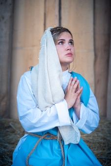 Caucasian woman representing virgin mary while praying in a crib