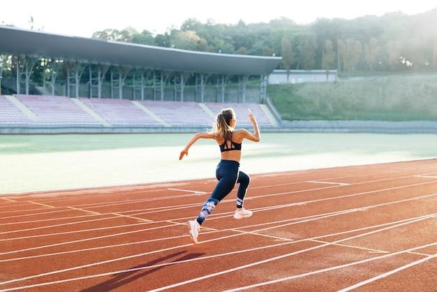 경기장의 스포츠 트랙에서 유산소 운동을 하는 운동복을 입고 달리는 백인 여성