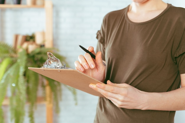 Caucasian woman's hands holds clipboard