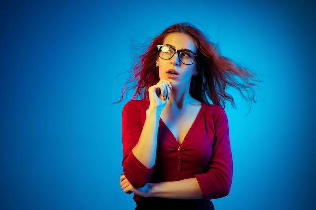 Ritratto di donna caucasica isolato su spazio blu in luce al neon