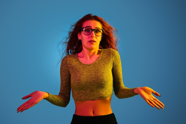 Caucasian woman's portrait isolated on blue studio background in neon light. beautiful female model with red hair in casual style. concept of human emotions, facial expression, sales, ad. uncertainty.
