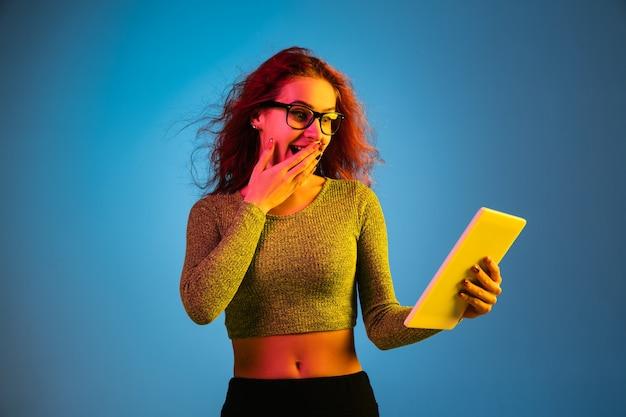 Ritratto di donna caucasica isolato su studio blu in luce al neon