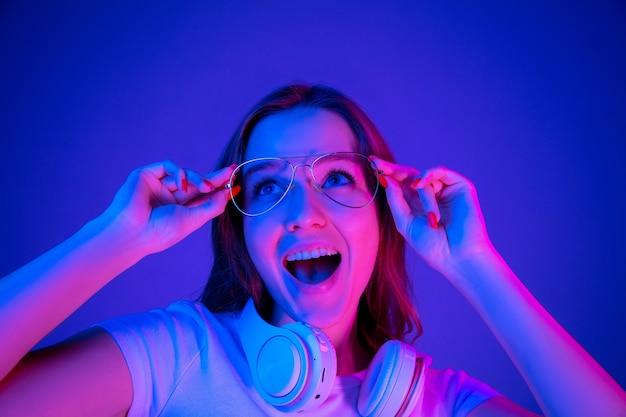 色とりどりのネオンの光の中で青い背景に分離された白人女性の肖像画。