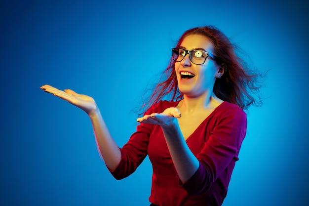 ネオンの光の中で青いスタジオの背景に分離された白人女性の肖像画。カジュアルな赤髪の美しい女性モデル。人間の感情、顔の表情、販売、広告の概念。あいさつ、ショックを受けた。