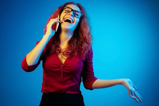 ネオンの光の中で青いスタジオの背景に分離された白人女性の肖像画。カジュアルな赤髪の美しい女性モデル。人間の感情、顔の表情、販売、広告の概念。電話で話します。