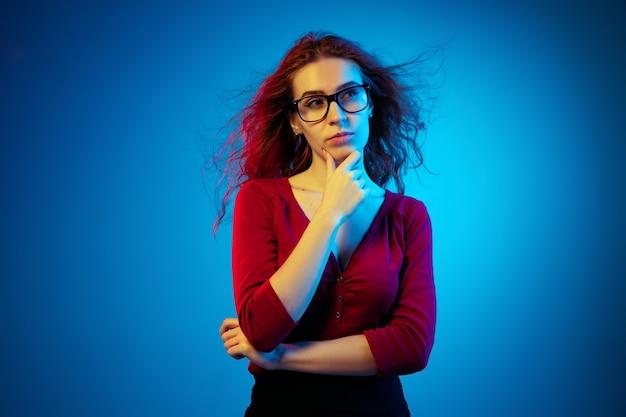 ネオンの光の中で青いスタジオの背景に分離された白人女性の肖像画。カジュアルなスタイルの赤い髪の美しい女性モデル。人間の感情、顔の表情、販売、広告の概念。思いやりがある。