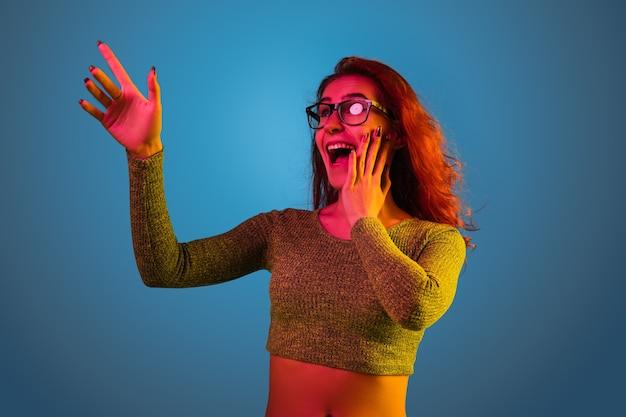 ネオンの光の中で青いスタジオの背景に分離された白人女性の肖像画。