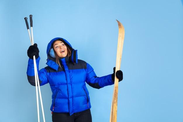 青いスタジオの背景、冬のテーマに分離された白人女性の肖像画