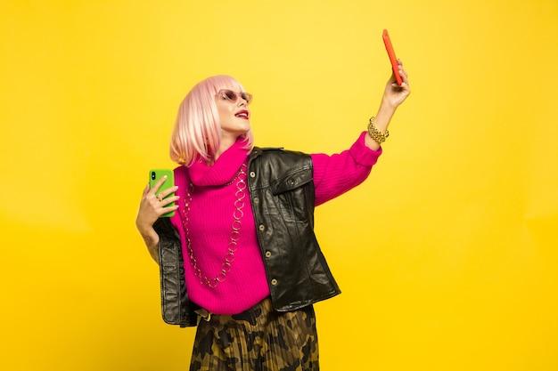 노란색 스튜디오 배경에 고립 된 백인 여자의 초상화, 영향력이 될