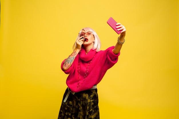黄色の背景に白人女性の肖像画。美しい金髪モデル。人間の感情の概念、顔の表情、
