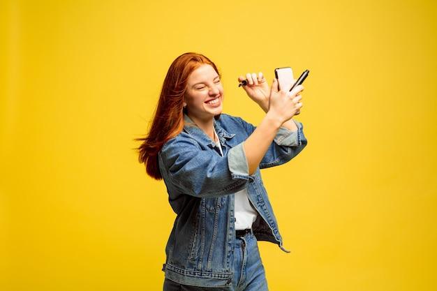 黄色の背景に白人女性の肖像画。美しい女性の赤い髪のモデル。人間の感情、顔の表情の概念