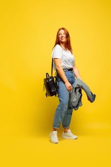 黄色の背景に白人女性の肖像画。美しい女性の赤い髪のモデル。