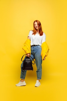 Caucasian woman's portrait on yellow background. beautiful female red hair model.