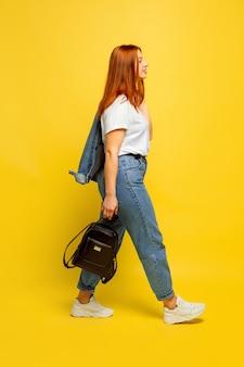 Ritratto di donna caucasica su sfondo giallo. bello modello femminile dei capelli rossi.
