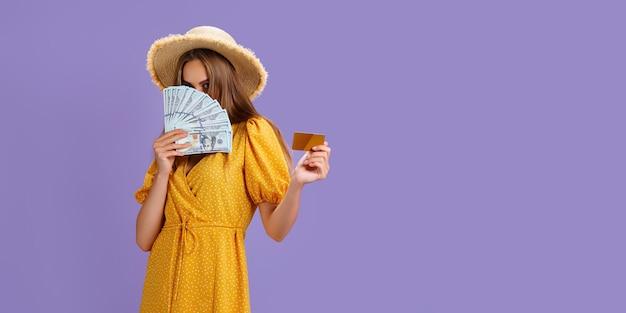 クレジットカードと紫の上に分離されたドルの現金のファンを保持している麦わら帽子をかぶっている白人女性...